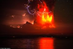 An electrical storm lights up the night sky as a huge column of ash and lava shoots out of...