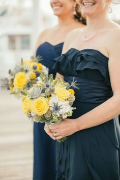 Navy blue bridesmaids dresses with yellow and blue bouquets