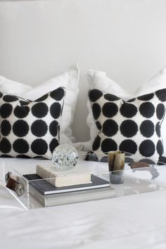A pair of polka-dotted pillows with white bedding.