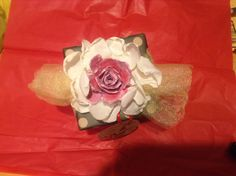 Gift wrap and bow idea that includes egg carton painted rose, melted fabric flower, and tulle.