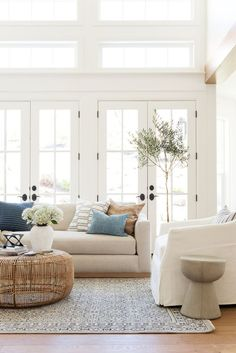 bright white cozy living room // natural light // French doors // while sofa // white armchair // wicker coffee table