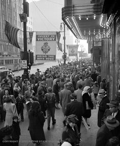 1945: An advertisement for war bonds hangs over shoppers at Woodward and State. Downtown Detroit