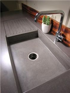 same dark concrete sink with drainboard, from different angles