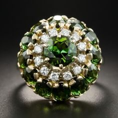 This singular and stunning cocktail bauble (just-for-fun-ring), dating from the mid-20th-century, is designed with a gleaming gold dome studded with flashing forest green tourmalines and a ring of sparkling round brilliant-cut diamonds. Unique and striking. The maker's mark indicates by Jones and Woodland. 3/4 inch diameter, currently ring size 5 3/4+.