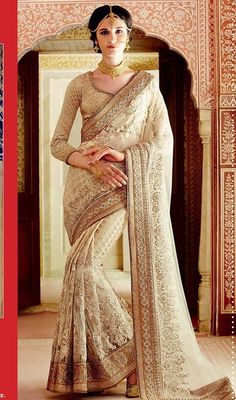 Become an enchanting secret dolled up in this cream color embroidered banarasi silk and net designer sari. Beautified with floral patch, lace, resham and stones work. #newpartywearsari #charmingpartysaris #beigecolornetsaree