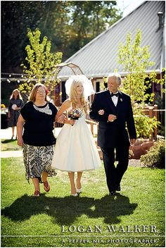 Black, white and red wedding colors.  Retro 1950s inspired wedding.  The bride walks down the aisle escorted by her mother and father.