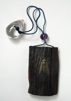 """Depicting a cicada alighted on a piece of wood, the inroopens at the side to reveal five tiny drawers. A basket outlined in gold appears on the back. The netsuke is crystal carved in the shape of an eggplant; the sliding clasp (ojime) is amethyst.Source: """"Japanese Objects,"""" in Journeys East: Isabella Stewart Gardner and Asia, edited by Alan Chong and Noriko Murai (Boston: ISGM and Gutenberg Periscope, 2009): 414."""