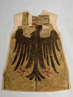 """""""Fahne Karls des Großen"""" (Heroldsrock), 14. Jahrhundert und um 1880 -- The embroidery is an example of a medieval original of unknown origin turned into a historicized construct. Regarded as Charlemagne's flag it was kept in the Neustadt am Main monastery until the 19th century. The embroideries no longer had their original form and were joined in a long strip. In ca. 1880 they were sewn together onto a new linen ground and were considered from then on as the oldest surviving herald's…"""