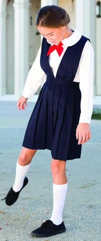 This classic skirt jumper with a v-neck shape has baked-in pretty knife pleats all around. Easy to dress and iron free.
