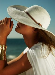 white hat and gold cuff bracelet