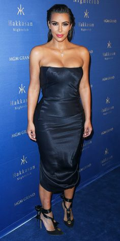 Spotted at a Las Vegas nightclub, Kim Kardashian West hit just the right balance between sultry and sophisticated with a formfitting silk dress and lace-up pumps in elegant black satin. The crowning touch? Relaxed, effortlessly swept back hair to offset the tightly wound ribbons and exact draping.