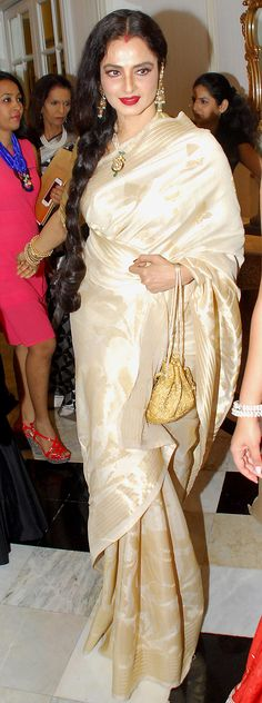 Rekha in a cream silk saree teamed with braided hair, statement necklace and gold potli bag.