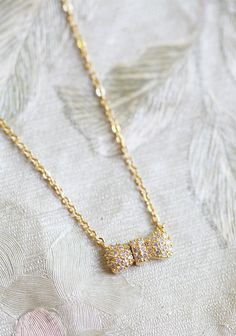 """This is a great bridesmaids gift! Promises Gold Bow Necklace 22.99 at shopruche.com. Perfected with delicate details, this gold colored necklace holds a diminutive bow shaped charm with sparkling rhinestone accents.  16"""" long"""
