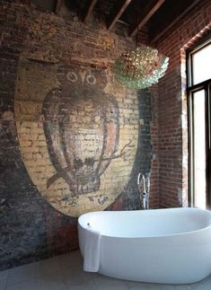 what a bathroom: floor to ceiling windows, original wood rafters supporting a high ceiling, exposed brick with a gigantic owl motif, and coke bottle chandelier surrounding a roomy white tub. #upcycle #animalistic