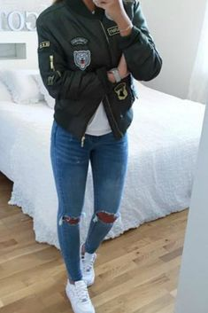 a teen girl wearing a fall outfit taking a picture in a mirror with her camera phone wearing a green patch bomber jacket and ripped skinny jeans and white sneakers