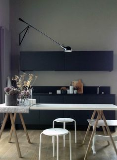 grey walls + black cabinetry + white table + stools + long-arm lamp