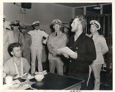 1943- Crew of U-352, sunk by the U.S. Coast Guard cutter ICARUS, in the Charleston Navy Yard barracks. Leutnant zur see (Sonderführer) Oskar Bernhard, navigator aboard U-352, addresses the crew in the filling out of the Basic Personnel Record which he holds in his hands.