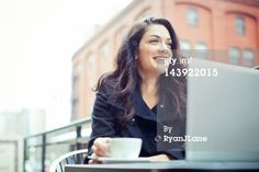 Title: Coffee Break Business Woman Outdoors Caption: A happy young beautiful professional sits at an outdoor cafe in the city, holding a cup of espresso coffee and smiling while taking a break from her laptop computer. Horizontal with copy space. SELECTIVE FOCUS ON FACE. Creative image #: 143922015 License type: Royalty-free Photographer: RyanJLane Collection: Vetta Credit: RyanJLane