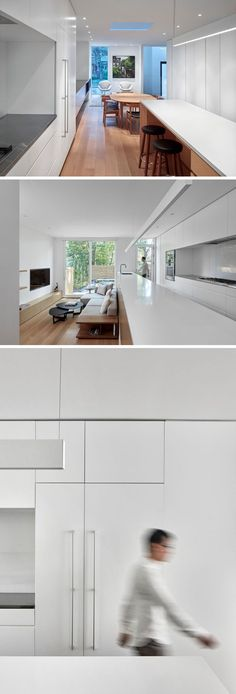 White minimalist cabinets fill the wall, and a long kitchen island with space for seating provides a backdrop for the living room that's stepped down from the kitchen. #WhiteKitchen #MinimalistKitchen #LivingRoom