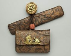 Tobacco-pouch and pipecase with embossed designs; netsuke; kanamono; ojime  Japanese, Edo period–Meiji era, mid to late 19th century (before 1889)  Unno Bisei II, Japanese, 1864–1919, Main material: embossed and painted leather; other metals: gold, silver, shakudo and copper; ivory netsuke with gilt snake; decorative technique: uchidashi; iroe takazogan, MFA