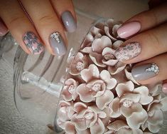 Alternating pink and gray winter nail art design. The nails are painted in light pink and gray colors in alternating method with the base and the details that are painted on top. The details look like beautiful flowers that have silver beads added on them.
