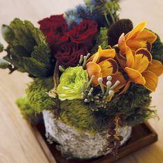 Urban-rustic art is sculpted of moss, copper Cymbidium orchids, chartreuse and deep red roses, thistle, cape baubles, dry sponge mushrooms, fig branches and date stems wrapped in an Aspen bark sheet.
