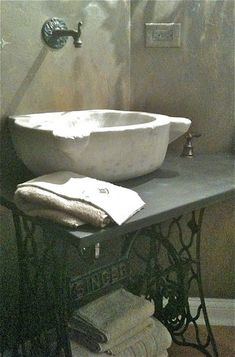 Tumbled marble bathroom sink sits on a vintage Singer sewing machine base