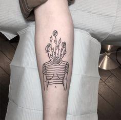 Tatuagem em preto e branco, com estilo minimalista, de um corpo com flores na cabeça