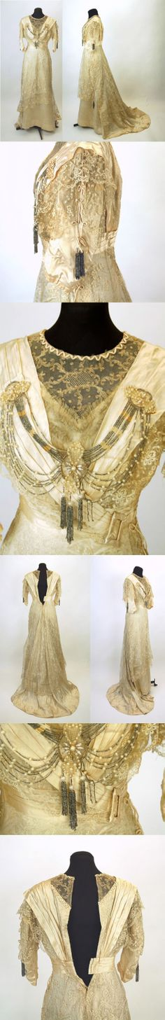 1910s gown in champagne color silk and lace. Polished cotton lining with bodice boning. Circular weights the size of quarters are sewn onto the hem of the underskirt, every 10 inches. The dress closes in the back with hooks and eyes located on the cotton lining and on the lace. From ebayseller: zannew