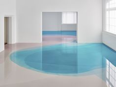 "Painter Peter Zimmermann has moved his colorful hues from canvas to floor in his latest exhibition ""Freiburg School,"" at the Museum für Neue Kunst in Freiburg, Germany. The installation is composed of bright blue, pink, and peach resin that appears like a candy-colored lagoon beneath the feet of mus"