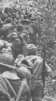 Japanese soldiers, on the right, march south into Bataan as POWs on the march pass on the left.