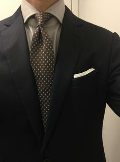 Navy jacket, white shirt with grey dress stripes, brown tie with light blue dots