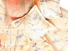Diese Kissenhülle aus Baumwollsatin ist anschmiegsam und verzaubert durch ein florales Muster auf cremefarbenen Grund.