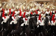 Members of the Household Cavalry arrive outside the Palace of Westminster for the State Opening of Parliament