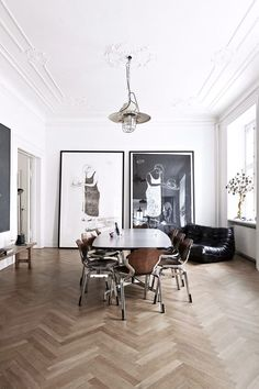 A classic but modern apartment with a dining room featuring herringbone parquet flooring and amazing artworks.