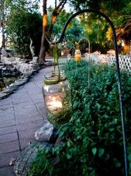 An easy inexpensive way to add character and a little light- mason jars hung from a tall iron hook, oh so chic as a backyard accessory.