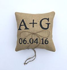 A rustic wedding is totally complete with our personalized burlap ring pillow. This pillow is made with natural burlap and stenciled with your initials and wedding date in the paint color of your choice. A string of jute adds that simple touch for your rings. This ring bearer pillow