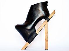 Ein schwarzer Schuh auf einem Holzstab.