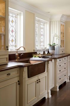 love the beadwork on side of cabinets and dark wood countertops with the white cabinets