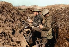 Pigeon post: Pigeons were often used to carry messages from the front line when radio, Morse code and human runners had failed. Here an officer (far right) writes a message as the pigeon's handler, having removed the bird from its cage, holds it upside down to attach the note