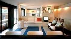 White walls and ceiling, bold floor color, lights near the ceiling on the walls.