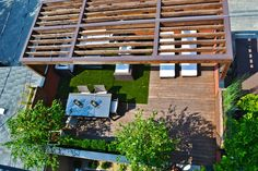 ~ This sunny roof deck project features multiple seating areas, an outdoor dining table and a custom fire pit ~ A cedar pergola offers partial shade above decking & artificial grass, making this rooftop deck a perfect space for entertaining and sun bathing in the Windy City ~