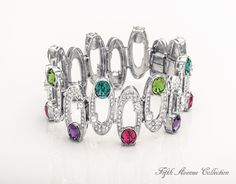 """""""Lights, Camera, Action"""" is a cuff bracelet set in a wave of Swarovski's clear and colored crystal. www.fifthavenuecollection.com/sleeuw"""