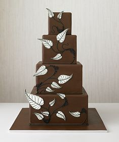 """""""White leaves with finely illustrated lines cascade down a square-shaped chocolate cake."""""""