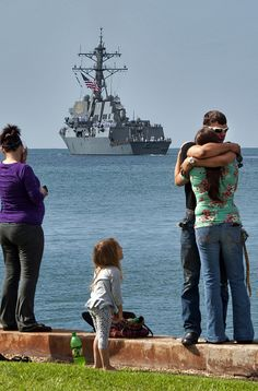 Family members of Sailors aboard the guided-missile destroyer USS Chung-Hoon (DDG 93) observe the ship's departure from Joint Base Pearl Harbor-Hickam for an independent deployment to the Indo-Asia-Pacific region. The ship and its crew will conduct integrated operations in conjunction with allies and partners. (U.S. Navy photo by Mass Communication Specialist 3rd Class Diana Quinlan/Released)