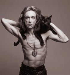 Ageless rock rebel Iggy Pop wearing his feline pet on his shoulders.