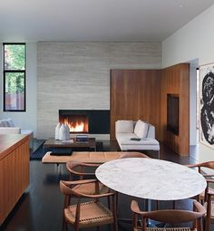 "In the great room of architect David Jameson's Maryland residence, the living and dining areas merge, with little more than a change in ceiling height to signal a division. ""The puzzlelike interlocking of the stone fireplace and the teak casework continues the exterior design language,"" he says."