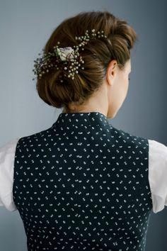 Die eingerollte Hochsteckfrisur passt perfekt zu romantischen Dirndl-Outfits. Eingearbeitete Blumen machen den Look perfekt.