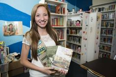 Erica Guzman, 18, of Parkville, holds some books in the library that she created for her Girl Scout Gold Star project at ReStart, 918 E. 9th Street, on Thursday, June 26, 2014, in Kansas City, Missouri. the Girl Scout Gold Award, the female equivalent of the Eagle Scout award.