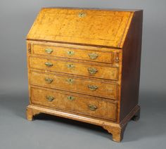 """Lot 1216, A Queen Anne walnut bureau, the fall front revealing a well fitted stepped interior above 3 long graduated drawers, raised on bracket feet 40""""h x 36""""w x 20""""d, est  £200-300"""